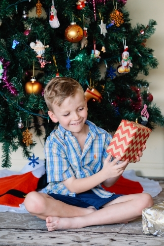 Little boy looking at a Christmas gift excitedly