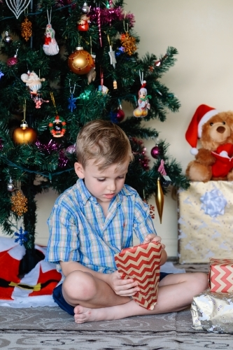 Little boy opening a gift on Christmas day next to the Christmas tree