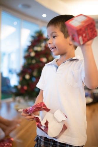 Little boy opening Christmas presents at home
