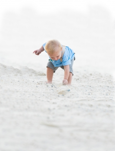 Little boy picking up a shell on the beach