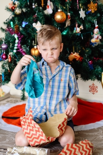 Little boy pulling a face, unhappy with a gift of underpants he has received on Christmas day