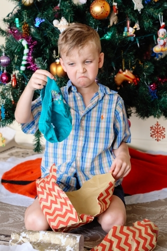 Little boy pulling a sad face, unhappy with a gift of underpants he has received on Christmas day