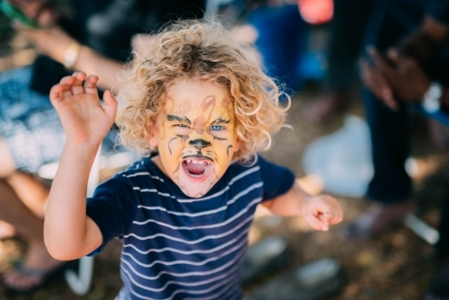 Little boy roaring with face paint