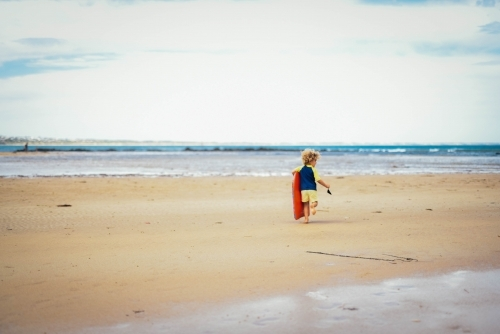 Little boy walking toward the water at the beach