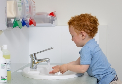 little boy washing his hands at hand basin with soap