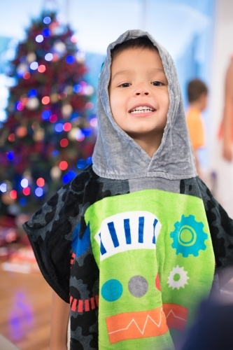 Little boy wearing a hooded towel he received for Christmas