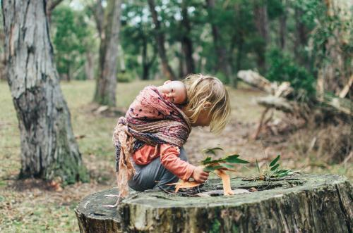 Little girl climbing tree stump with dolls in the bush