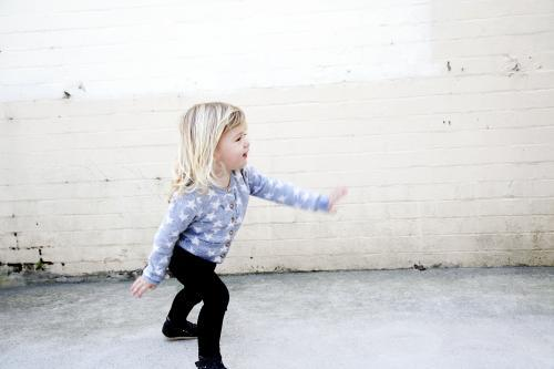 Little girl dancing in front of brick wall