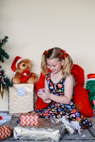 Little girl happily looking at a Christmas gift she has unwrapped