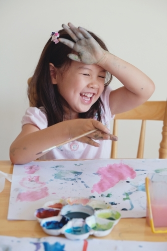 Little girl having fun painting at home