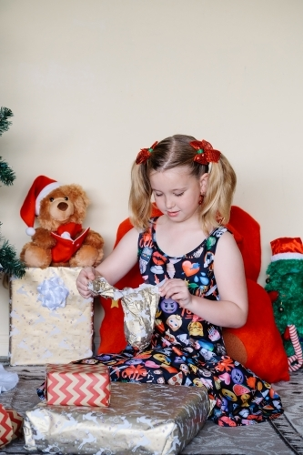 Little girl in an emoji dress opening a Christmas present