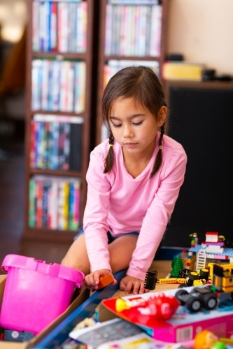 Little girl in pink playing with toys at home