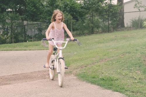 Little girl learning to ride her new bike, winking at camera