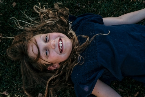 Little girl lies down on the grass