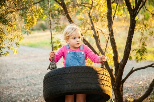 Little girl on tyre swing in afternoon light