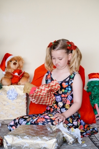 Little girl unhappy with a Christmas gift she has opened