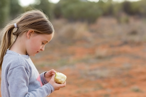 Little girl with apple outside with red dirt