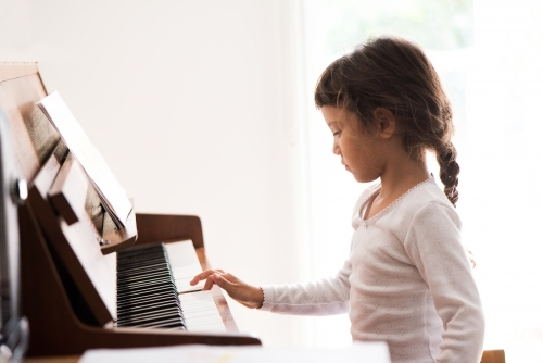 Little girl with Asian ethnicity learning to play the piano.