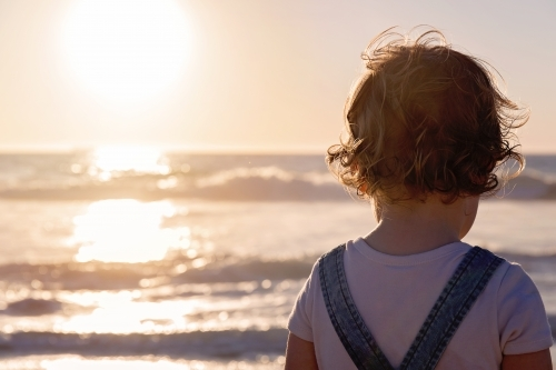 Little Girl With Curly Hair Looking Out To The Ocean At Sunset