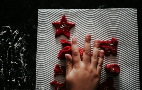Little hands with red Christmas sweets