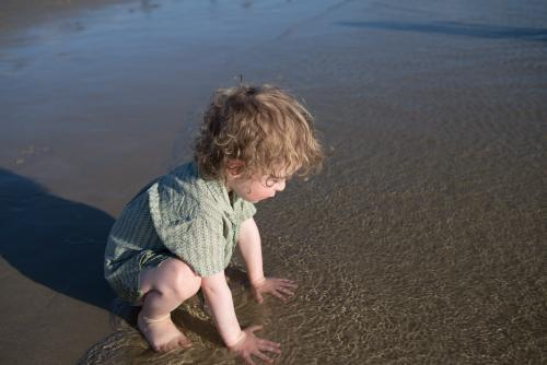 Young boy wearing a shirt crouching in shallow water at the beach