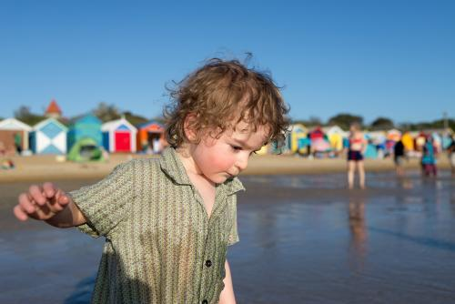 Little boy wearing a shirt standing in the ocean with colourful bathing boxes on the beach