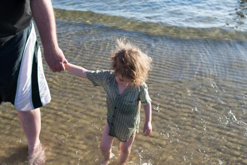 Young boy in a shirt with sunlit hair holding his father's hand at the beach