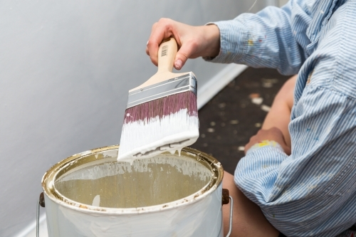 Loaded paintbrush dripping with white paint