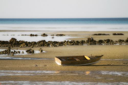 Lone wooden boat sitting on sand at low tide