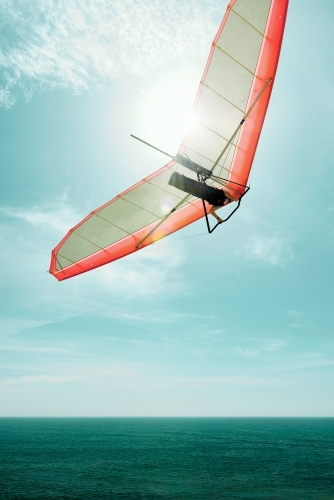 Hang gliding into the sun with a red glider