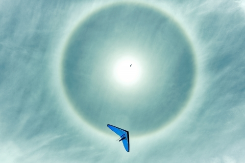 Hang gliding with sun halo on a beautiful day