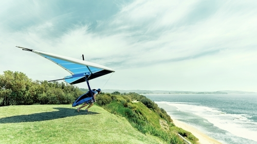 Hang glider taking off a cliff by the ocean