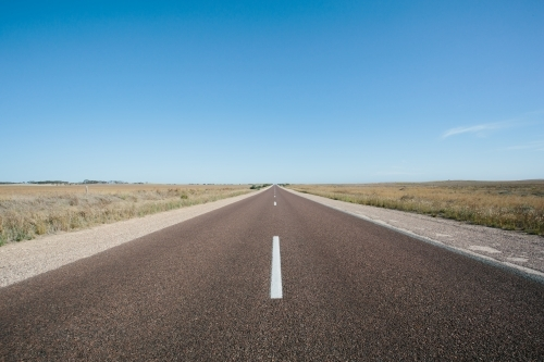 Long straight empty road through rural land