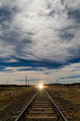 Looking down a Railway track with shining light in the distance on a starry cloudy night