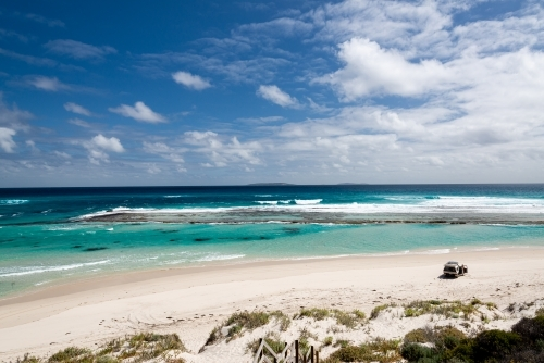 Looking down and out on a view of  man with 4wd vehicle on an isolated beach with turquoise lagoon