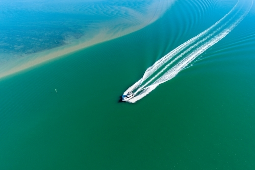 Looking down on a powerboat in estuary.