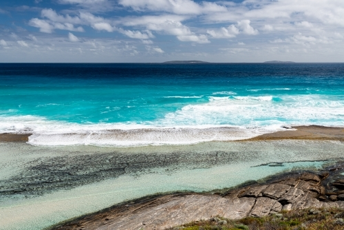 Looking down on turquoise water flowing into a rockpool