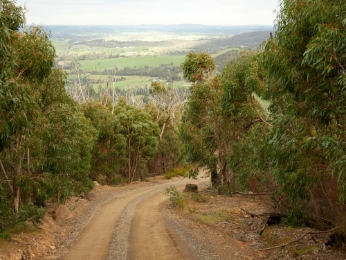 Looking Down Steep Gravel Road Toward Distant Farmland
