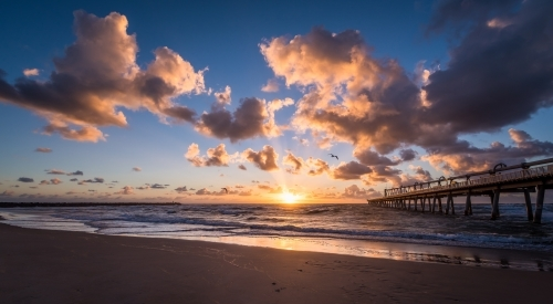 Looking out at sunrise from a beach with pier