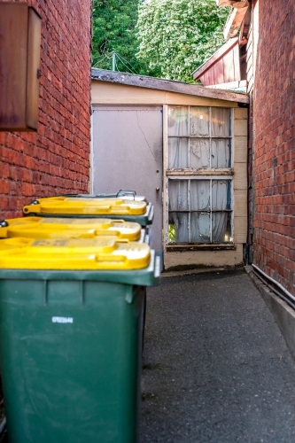 Looking past some wheelie bins to a small cottage garden entrance