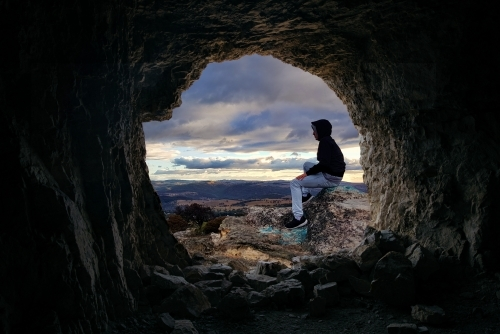 Looking through a cave to a male sitting on a rocky outcrop that looks over the valley