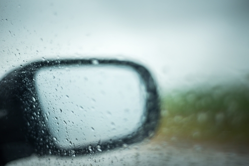 Looking through car window at side mirror in the rain
