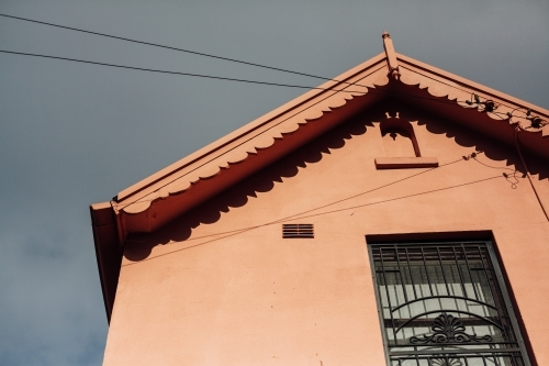 Looking up at roof of orange home against grey sky