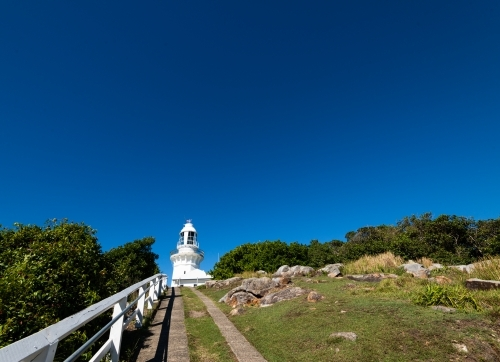 Looking up path to white lighthouse with deep blue sky
