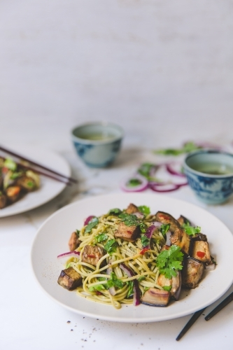 Low angle of cold soba noodle, eggplant and parsley salad with green tea on white background