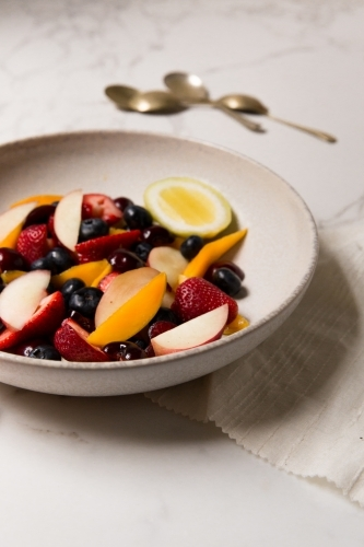 Low angle of styled, naturally lit and colourful mixed berry and stone fruit salad on marble table