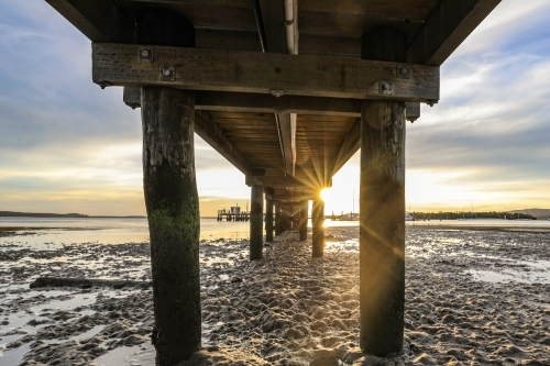 Low angle view of timber jetty leading to sunset through pylons