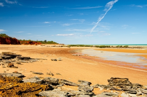 Low tide on an orange sandy beach with red cliffs, rocky foreground and blue sky