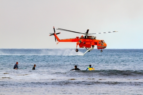 A water-bombing helicopter filling its water tanks from the ocean as surfers watch off Coledale, NSW