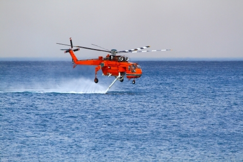 A water-bombing helicopter filling its water tanks from the ocean off Coledale in the Illawarra, NSW